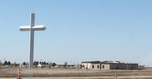 Gigantic cross next to a church in the middle of nowhere.